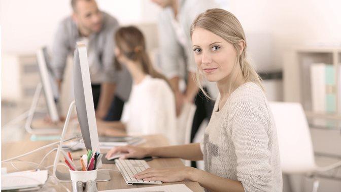 Zwei an Computern sitzende Frauen, dahinter sich unterhaltende Männer